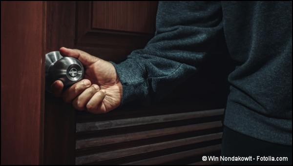Man's hand on door knob, trying to open door