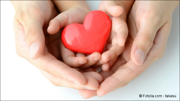 Heart cupped by a child's hands cupped by an adult's hands
