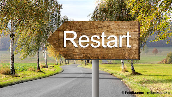 The word Reset on a pointing wooden sign by a road