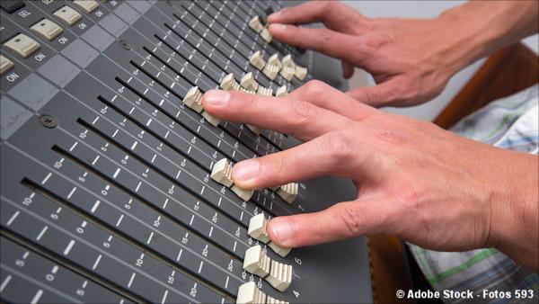 Hands adjusting professional studio mixing console