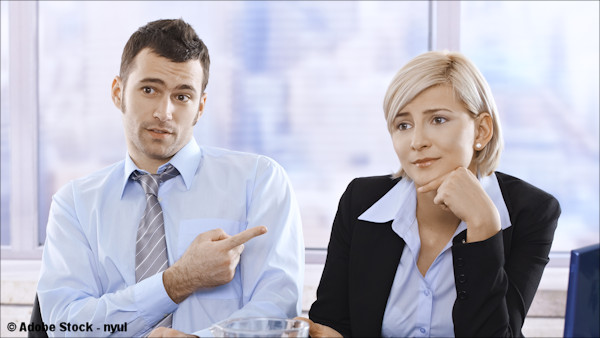 A business man pointing his finger in blame toward a businesswoman