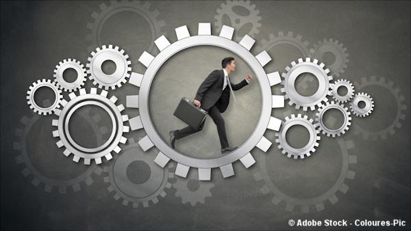 Business man inside gears (hamster wheel metaphor)