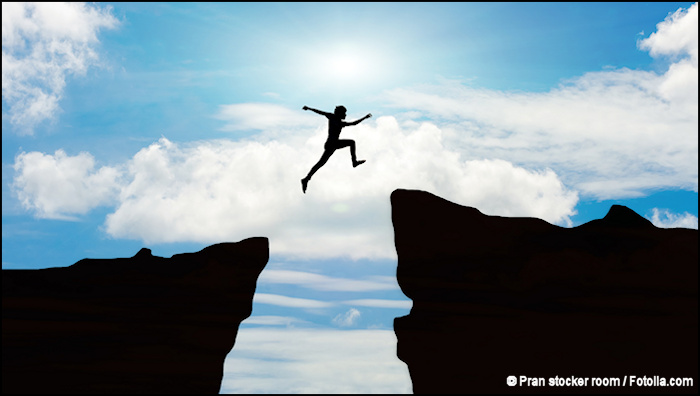 Silhouette of man jumping over gap between two cliffs.