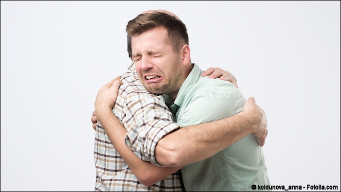 Adult son crying on his father's shoulder
