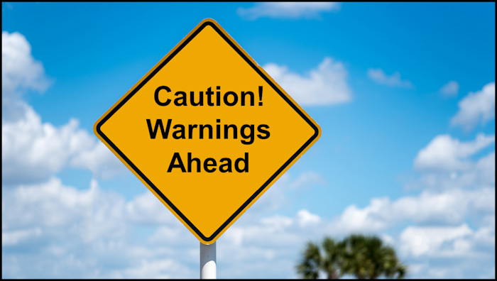 """Yellow diamond warning street sign with the words, """"Caution! Warnings Ahead"""""""