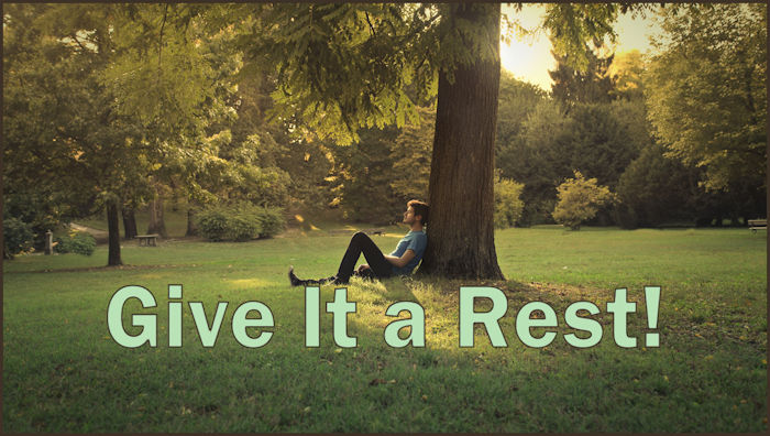 """The words """"Give It a Rest!"""" superimposed on a photo of a man sitting on the ground, resting, with his back against a tree in a green field."""